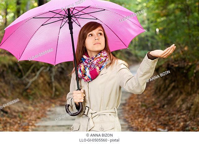 Beautiful girl with umbrella checking for rain, Debica, Poland