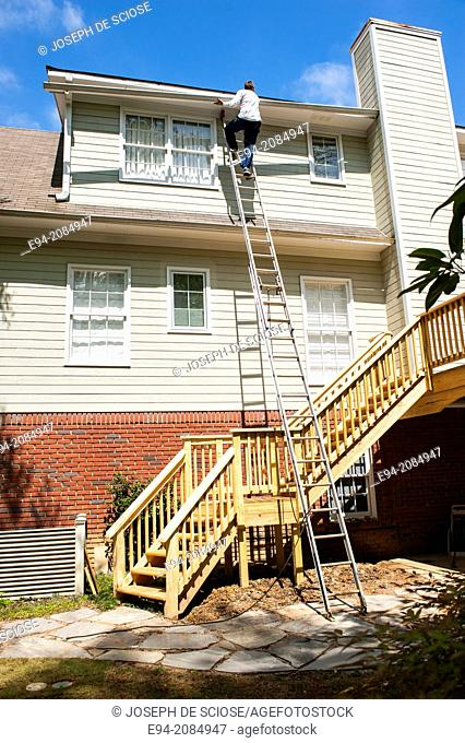 A man standing on a ladder on the side of a house lifting a drain gutter