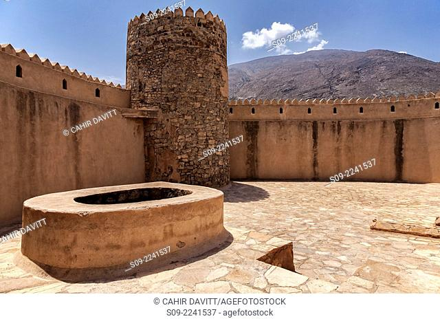 View of the battlements, tower, well and courtyard of Rustaq Fort with the Hajar Mountains in the background, Rustaq, Al Batinah South Governorate, Oman