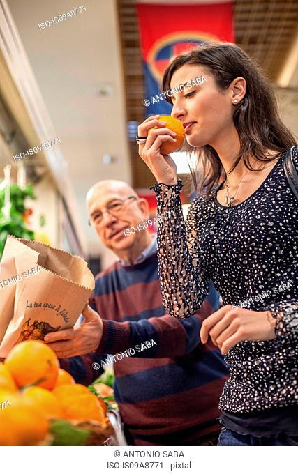 Woman smelling fresh oranges in market