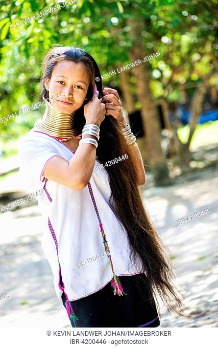 Young Kayan hill tribe woman does her hair in the morning, Chiang Mai, Thailand