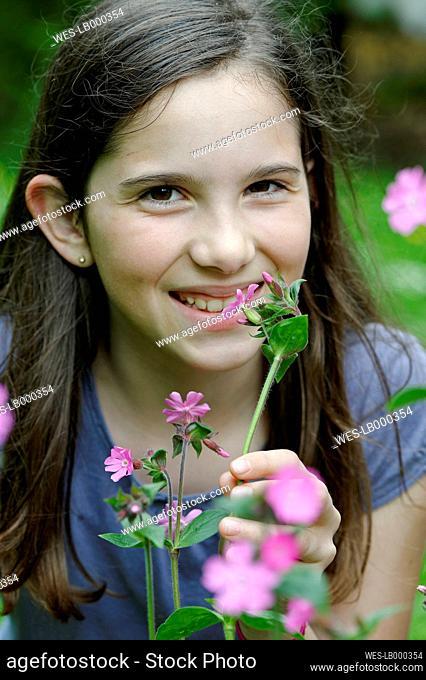 Girl smells at a spring flower