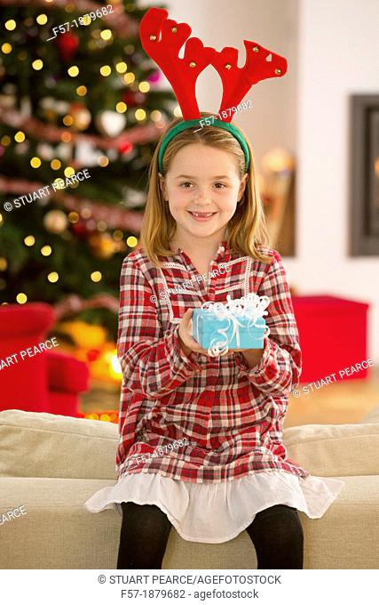 Young girl holding a gift at Christmas time