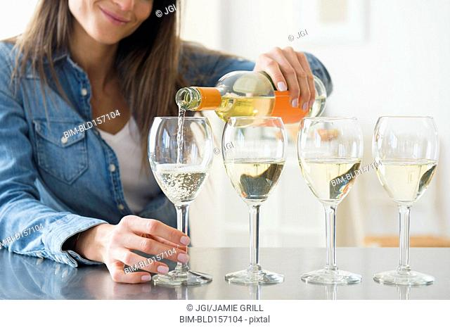 Caucasian woman pouring glasses of white wine