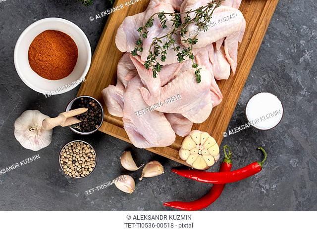 Raw chicken on cutting board with herb and spices