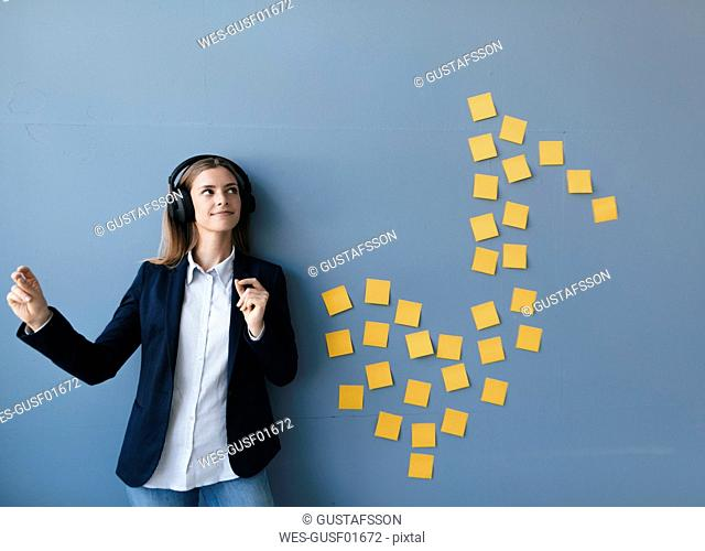Young businesswoman wearing headphones, listeining music