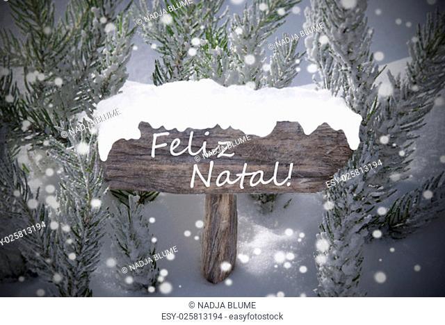 Wooden Christmas Sign With Snow And Fir Tree Branch In The Snowy Forest. Portuguese Text Feliz Natal Means Merry Christmas For Seasons Greetings