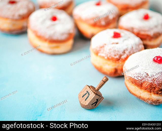 Jewish holiday Hanukkah concept and background. Hanukkah food doughnuts and traditional spinnig dreidl or dredel on blue background