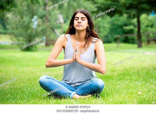 Young Woman Sitting On Grass Meditating In Park