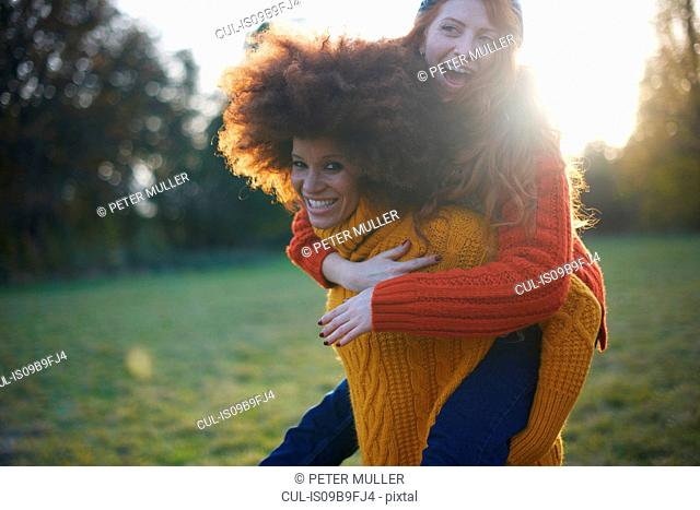Two young women, in rural setting, young woman giving friend piggyback ride