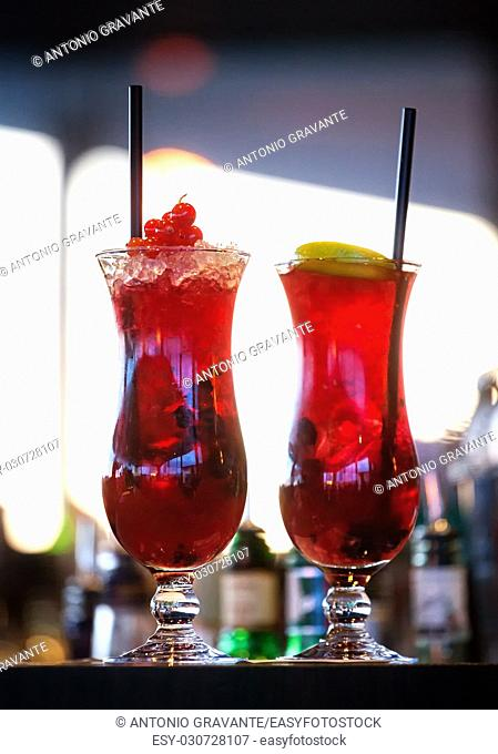 Two ice glasses of red alcoholic cocktail with fruits