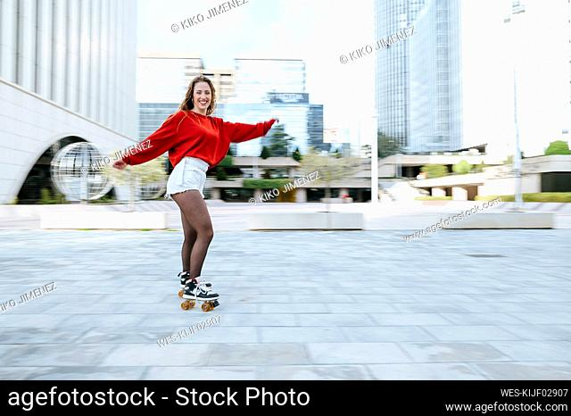 Portrait of happy young woman roller skating in the city