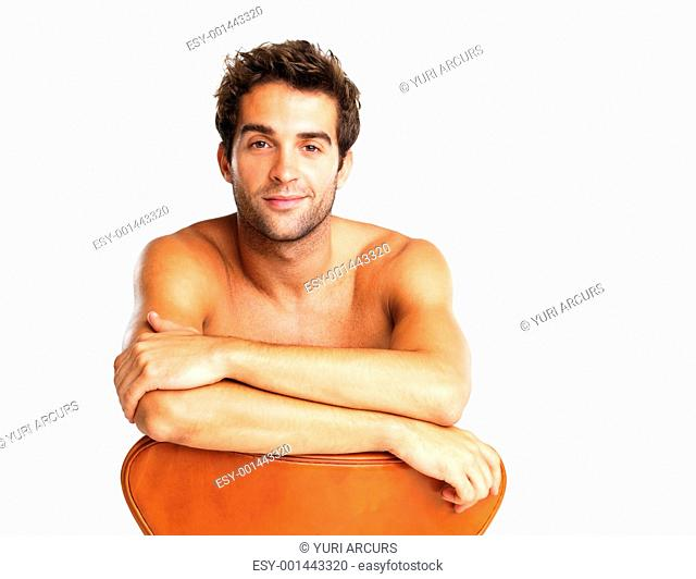 Attractive shirtless man sitting in chair