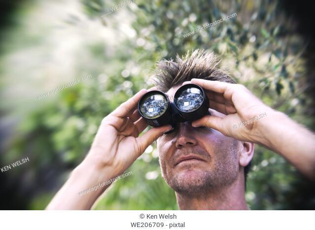 Man, 40-45, looking through binoculars