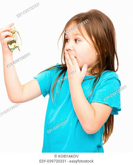 Little girl is looking at alarm clock while covering her mouth in panic, isolated over white
