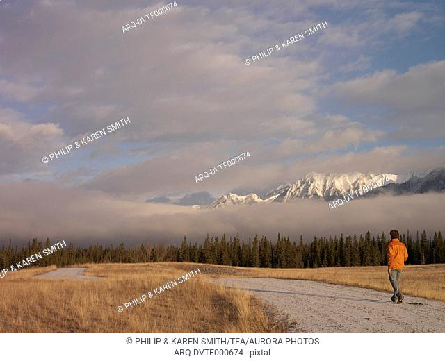 Man walks down windy road with fog and mountains in distance