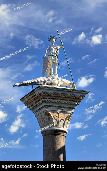 Venice, Venice Province, Veneto Region, Italy. Statue of St. Theodore atop granite column in the Piazzetta. He has a spear in his hand and his foot rests on a...