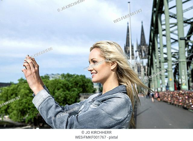 Germany, Cologne, young woman taking a picture with smartphone on Hohenzollern Bridge