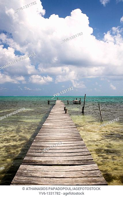 One of Caye Caulkers island wooden piers shoot on a bright day with blue sky and white clouds, Caye Caulker, Belize, Central America