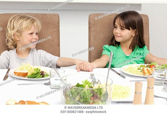 Cute brother and sister holding their hands before lunch in the kitchen