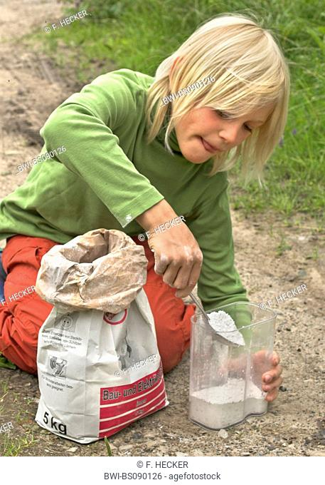 child making a cement copy of the trace of a roe deer, Germany