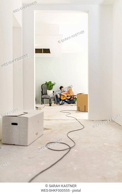 Couple with guitar relaxing on the floor of their unfinished new home