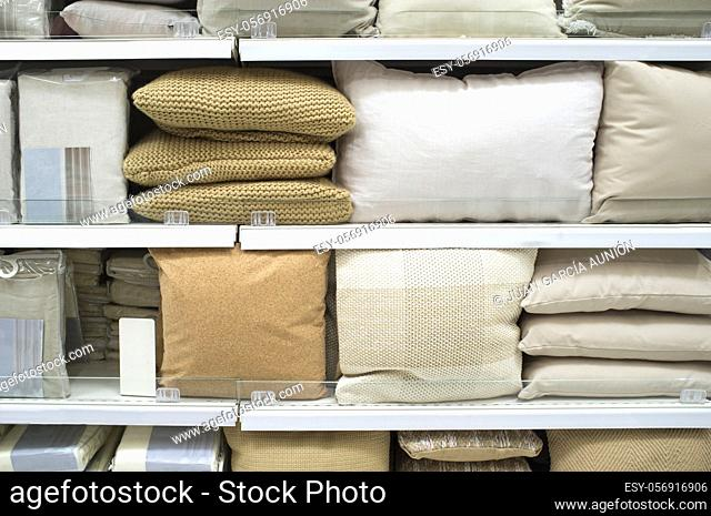 Bright pillows and bed wear on shelves. Selective focus