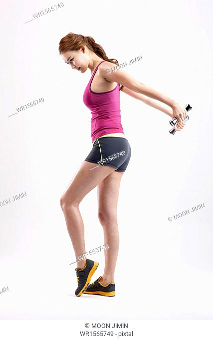 a woman doing exercise with dumbbell