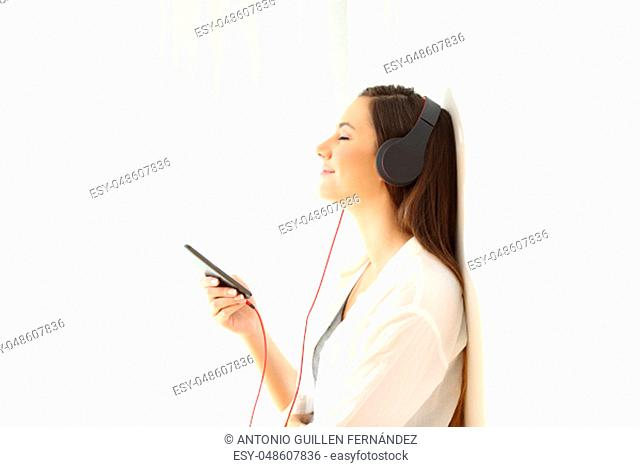 Side view portrait of a woman relaxing listening to music at home isolated on white at side
