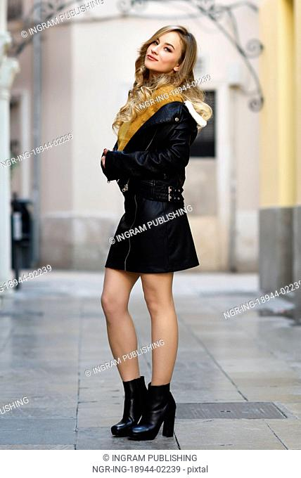 Blonde woman smiling in urban background. Beautiful young girl wearing black leather jacket and mini skirt standing in the street