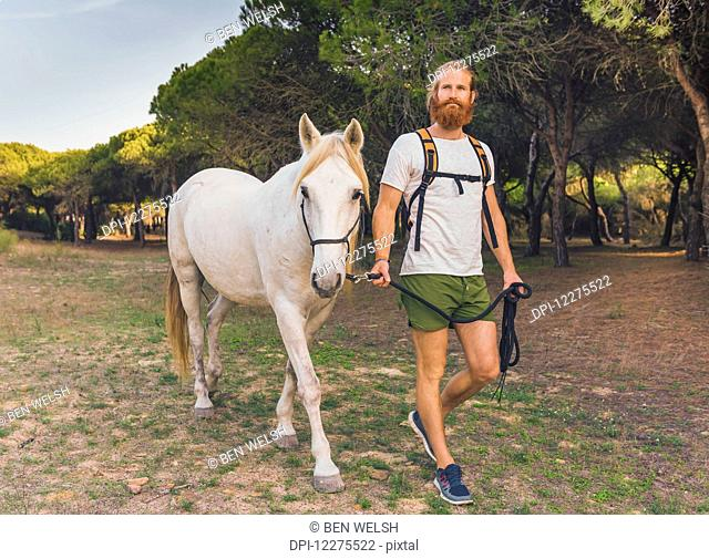 A man walking with a white horse; Cadiz, Andalusia, Spain