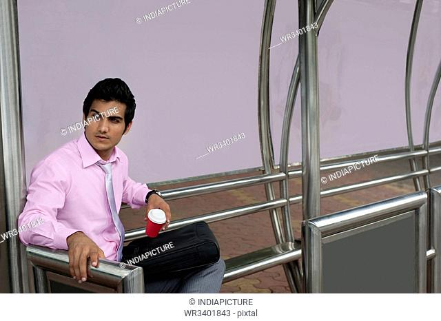 Businessman waiting at a bus stop