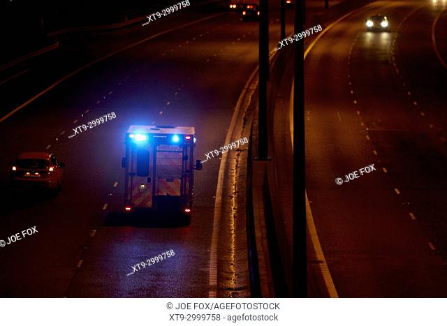 ambulance speeding along motorway with blue lights flashing in northern ireland uk