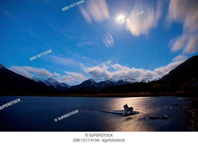 Lake surrounded with mountains at night, Mt Rundle, Banff National Park, Alberta, Canada