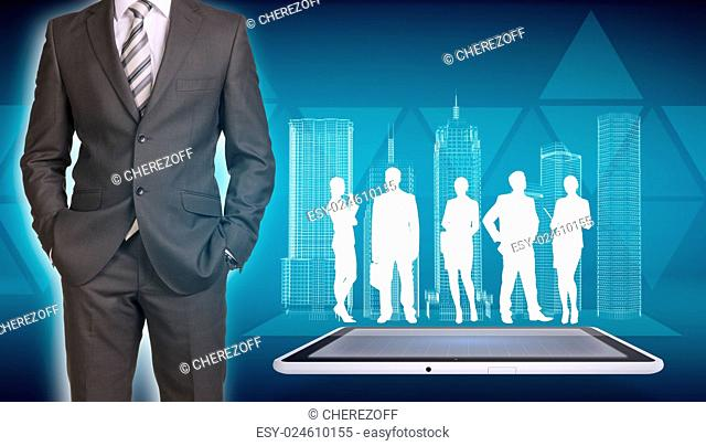 Businessman in suit standing and holds hands in pockets. Glowing wire-frame buildings and business silhouettes on screen tablet pc as backdrop