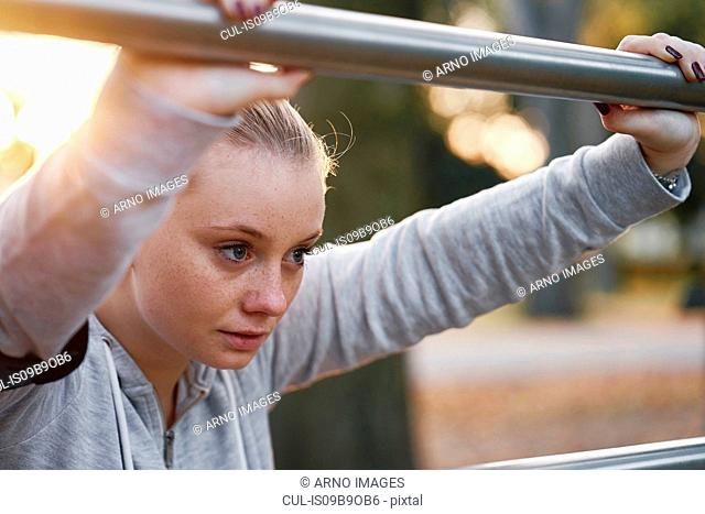 Young woman training, leaning against handrail in park