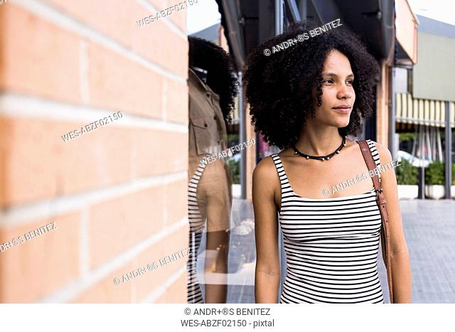 Portrait of young woman besides shop window
