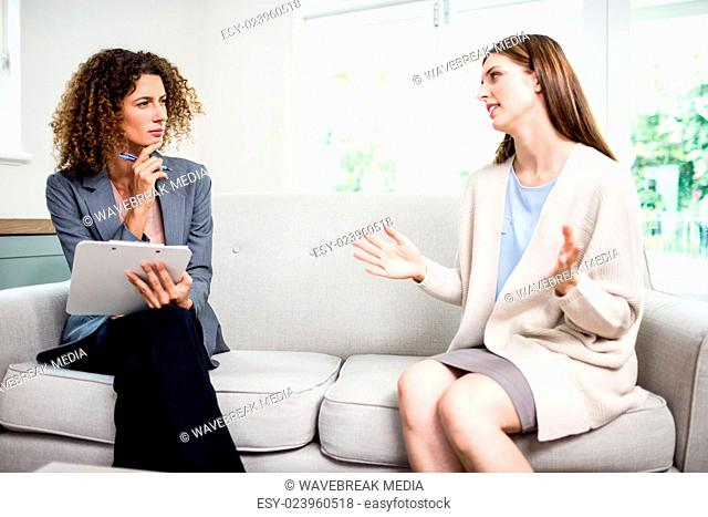 Young woman explaining problems to psychologist