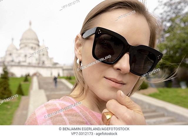 stylish blogger woman in front of touristic sight Basilica Sacré-Cœur, during fashion week, in city Paris, France, in city Paris, France