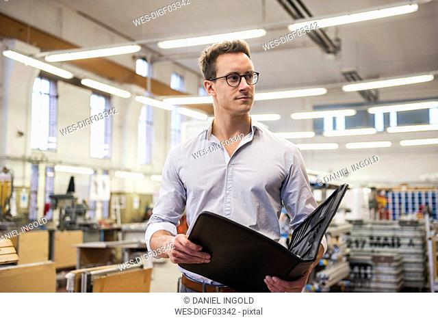 Young businessman in factory holding folder