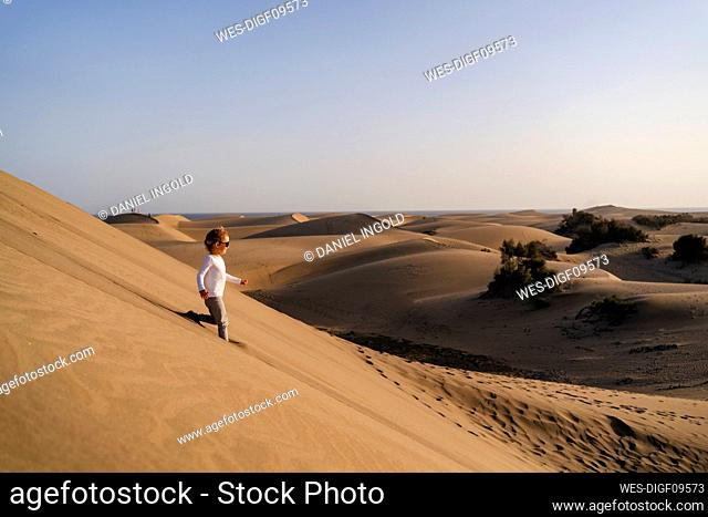 Girl running down sand dune, Gran Canaria, Spain
