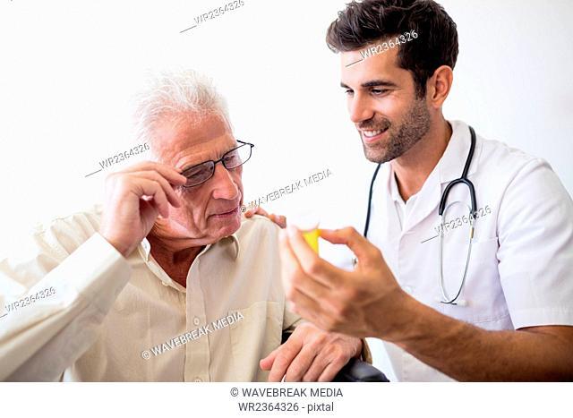 Nurse giving pills to senior man
