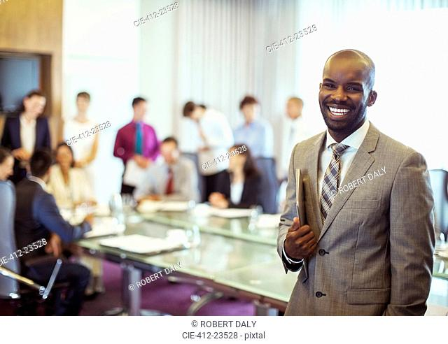 Portrait of smiling young man wearing suit and holding laptop in conference room