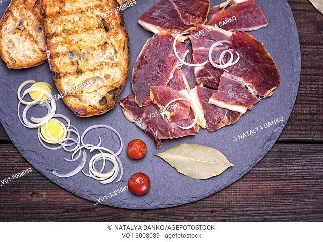 pieces of jamon and white fried bread for a sandwich on a black surface