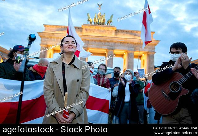 dpatop - 05 October 2020, Berlin: Opposition leader Svetlana Tikhanovskaya from Belarus sings a song with her supporters at the Brandenburg Gate