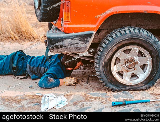 man lies under a 4x4 car on a dirt road, to see what the problem is