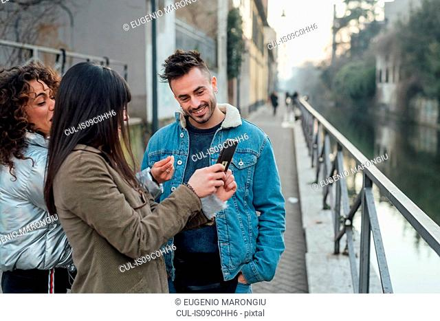 Friends using smartphone by river, Milano, Lombardia, Italy