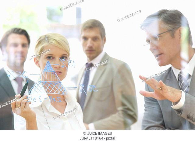 Businesswoman drawing diagram on glass in meeting room