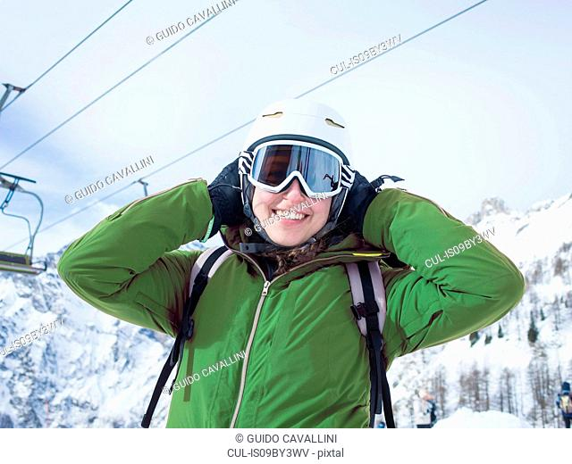c69bca9c656 Young woman skier wearing helmet and ski goggles in snow covered landscape