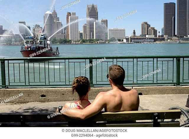 Couple on bench as boat streaming water drifts by on the Detroit River, Windsor, Ontario, Canada